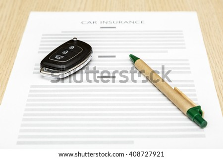 View of car keys and pen laying on a blank of insurance. - stock photo
