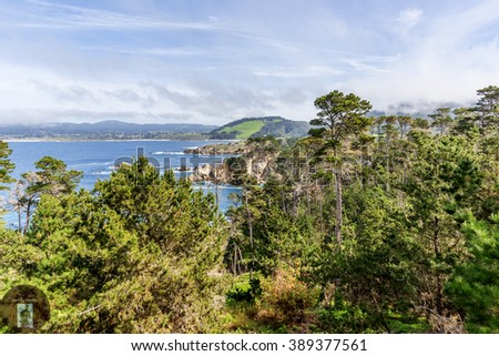 View of Carmel Bay, Highlands, with Cypress trees, blue sea, sky, clouds, and unusual rock and geological formations, as seen from the Whaler's Knoll Trail, at Point Lobos State Natural Reserve. - stock photo