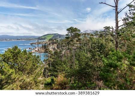 View of Carmel Bay, Highlands, with Cypress trees, blue sea, sky, clouds, and unusual rock and geological formations, as seen from the Whaler's Knoll Trail, at Point Lobos State Natural Reserve - stock photo