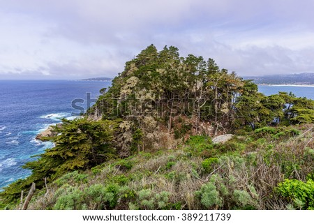 View of Carmel Bay, on a crisp spring morning, Cypress trees, blue sea & sky, & unusual rock and geological formations, as seen from the Whaler's Knoll Trail, at Point Lobos State Natural Reserve - stock photo