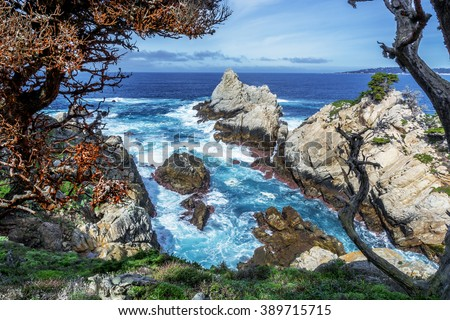 View of Carmel Bay through gnarly, twisted, crooked, Cypress trees with red lichen & Spanish moss growing on the branches, with unusual geological rock formations, blue seas, white clouds & blue sky. - stock photo
