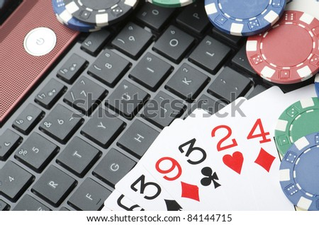 view of casino chips and cards to gamble and play online - stock photo