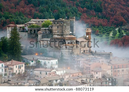 View of Castle of Arsoli and the village surrounded by morning fog with forest in autumnal colors in background - stock photo