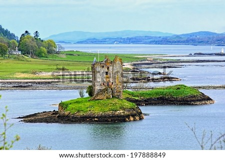 View of Castle Stalker surrounded by the lochs of Scotland              - stock photo