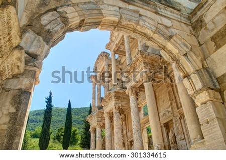 view of celsus library facade and green hill with cypress trees and blue sky through arch in Ephesus, Turkey  - stock photo