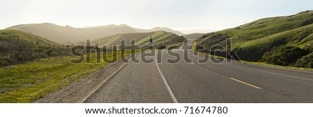 view of center line divider on highway cutting through coastal hills - stock photo