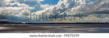 View of chemical plant across river estuary (panorama) - stock photo