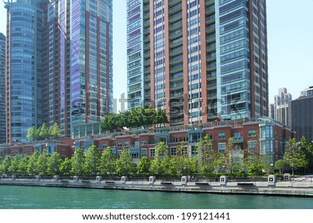 View of Chicago Riverwalk lined with green trees and rows of condos - stock photo