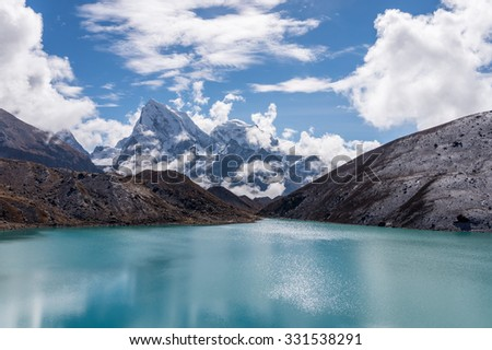 View of Cholatse and Taboche peaks and turquoise water of Gokyo lake (Dudh Pokhari) in Everest region, Nepal - stock photo