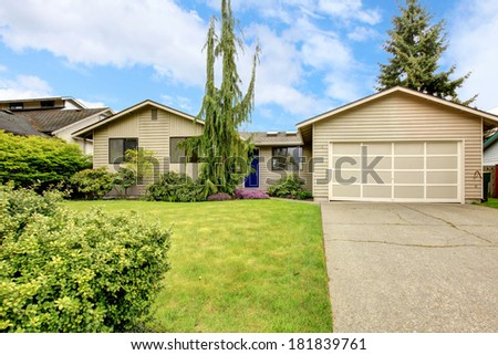 View of clapboard siding house with attached garage, concrete floor driveway and beautiful green lawn with tree and bushes