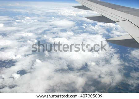 View of clouds and the earth from inside of the plane.