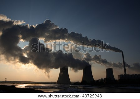 View of coal power plant against sun with several chimneys and huge fumes - stock photo