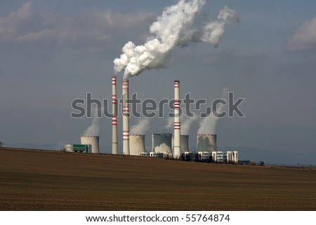 view of coal power plant over the field - stock photo