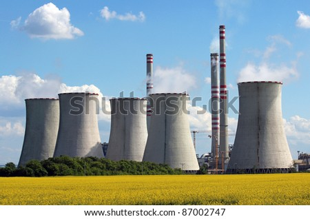 view of coal power plant over yellow agriculture field - stock photo