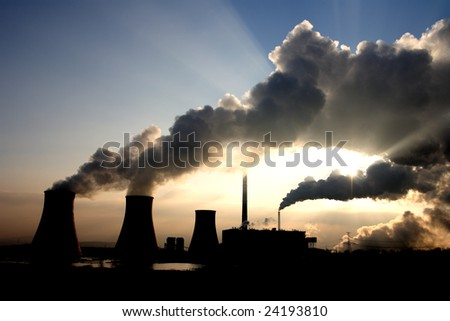 View of coal powerplant against sun with several chimneys and huge fumes.