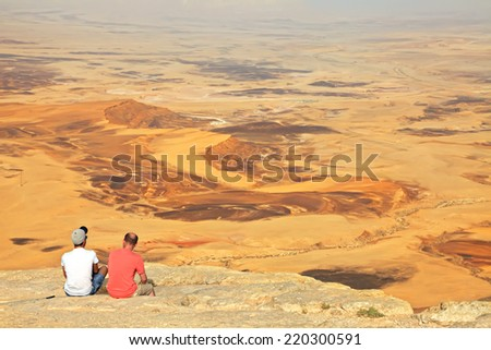 View of color sand stone Negev desert and people watching down from cliff.  National geological park HaMakhtesh HaRamon - Ramon Crater is the Largest crater- geological erosion land form in Israel  - stock photo