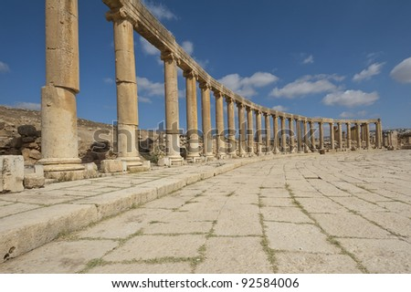 View of column in the Oval Plaza at the ancient Roman city of Jerash, Jordan. Note the columns that are offset on the left side of the photo. - stock photo