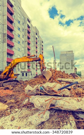 View of construction site (fixture, slabs, stacks, grab) in summer day - stock photo