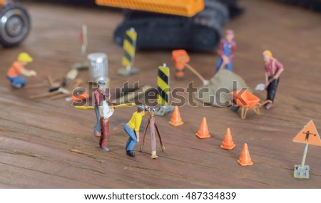 View of construction site of mini toy worker on wood background.
