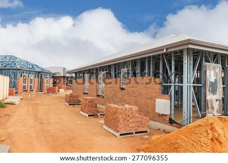 view of construction site with homes from brick with metal framing against a blue sky - stock photo