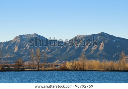 View of Coot Lake and the Flatirons Mountains golden morning sunlight in winter, with bare elms and cottonwoods on the far shore. - stock photo