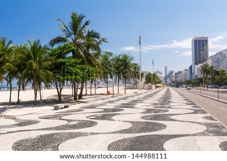 View of Copacabana beach with palms and mosaic of sidewalk in Rio de Janeiro. Brazil - stock photo