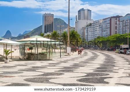 View of Copacabana beach with palms and mosaic of sidewalk in Rio de Janeiro. Brazil - stock photo