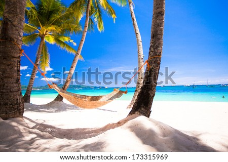 View of cozy straw hammock on the tropical white beach - stock photo