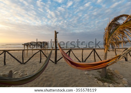 View of cozy straw hammocks on a tropical white beach with sunset light, Punta Sal near Mancora in Peru. - stock photo