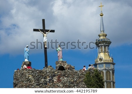 View of crucified Jesus Christ against cloudy sky, Mother of God and St. John under the Cross, tower of the Basilica of Our Lady of Lichen in the background, Poland - stock photo