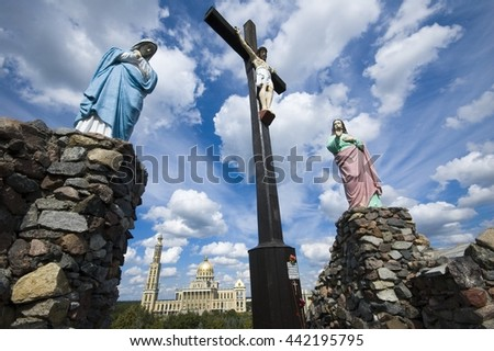 View of crucified Jesus Christ against dramatic cloudy sky, Mother of God and St. John under the Cross, Basilica of Our Lady of Lichen in the background, Poland - stock photo