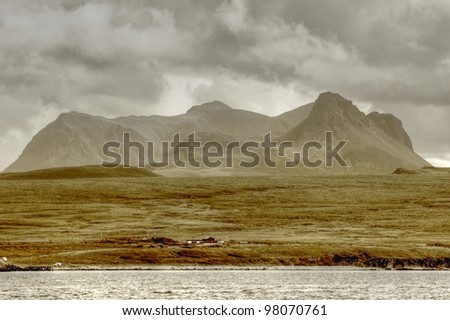 View of Cul Mor and Stac Pollaidh part of the Assynt area in Northwest Scotland, from the sea, showing stormy skies and isolated community - stock photo