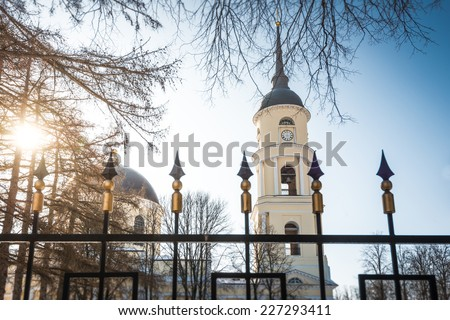 View of dome and bell tower of Orthodox Church through bars of fence. Winter sunny day, blue sky. Bell tower and church of pale yellow color with white details. - stock photo