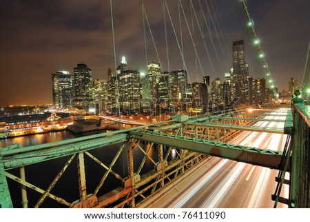 View of downtown Manhattan from the Brooklyn Bridge with traffic flying by. - stock photo