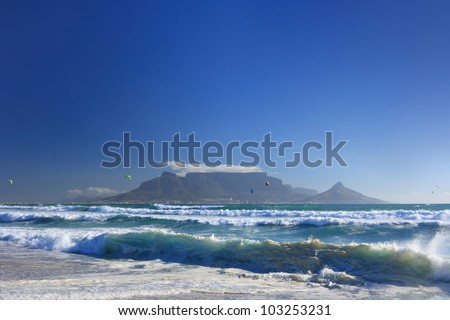 View of dramatic Table Mountain across Table Bay with big blue sky and shoreline waves in foreground. - stock photo