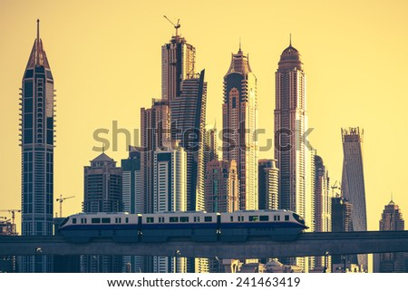 View of Dubai with subway and skycrapers at sunset. UAE - stock photo