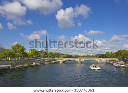 View of Eiffel Tower seen across  the Seine with old bridge and boat in Paris, France