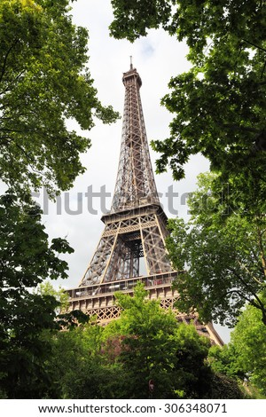 View of Eiffel Tower through summer green trees - stock photo
