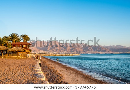 View of Eilat beach, Israel  over  Aqaba city, Jordan. - stock photo