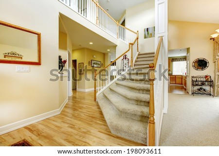 View of elegant staircase with wooden white and brown railings in modern large house - stock photo