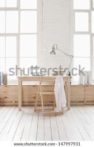 View of empty room with wooden table and chair in loft apartment - stock photo
