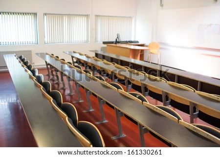View of empty wooden seats with tables in a lecture hall