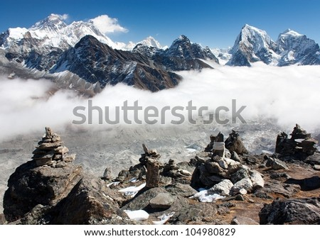 view of everest with stone mans from gokyo ri and clouds above ngozumba glacier - stock photo