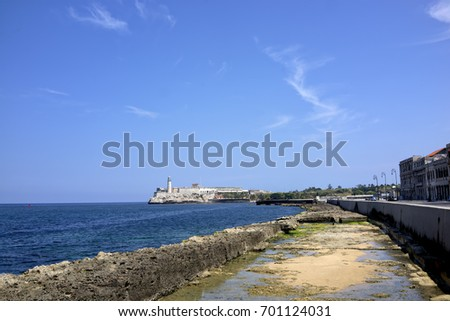 View of Faro Castillo del Morro - a lighthouse guarding the harbor of Havana, Cuba from the Havana Malecon - Havana's famous embankment promenade.