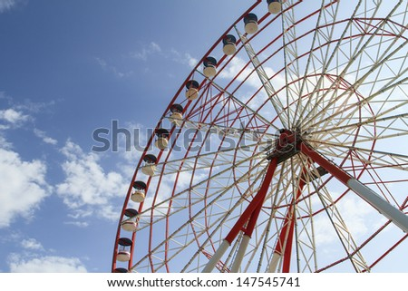 View of ferris wheel in funfair on sunny sky with cloudy background.