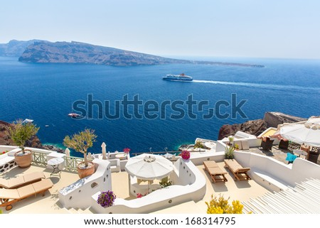 View of Fira town - Santorini island,Crete,Greece. White concrete staircases leading down to beautiful bay with clear blue sky and sea - stock photo