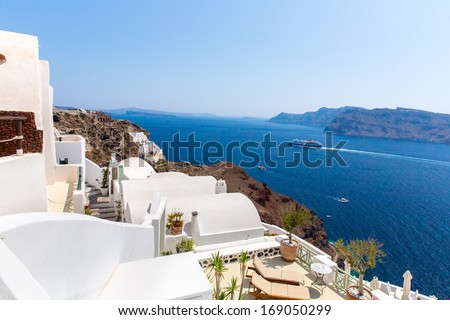 View of Fira town - Santorini island,Crete,Greece. White concrete staircases leading down to beautiful bay with clear blue sky and sea