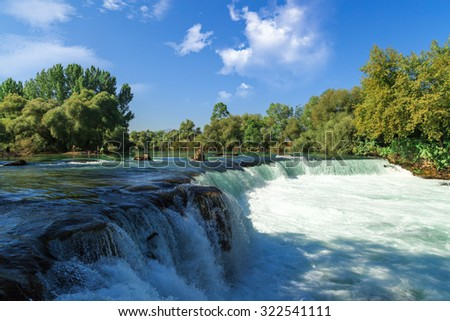 View of flowing Manavgat Waterfall in Antalya, Turkey, with green trees around, on cloudy blue sky background.