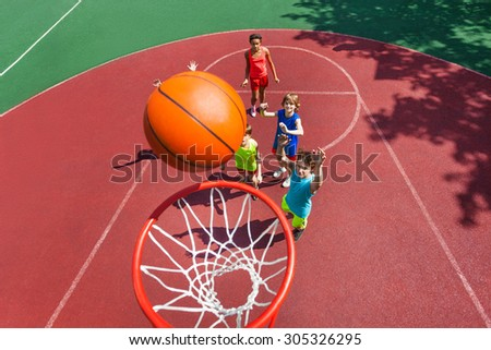 View of flying ball to basket from top, teens play - stock photo