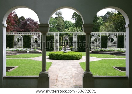 view of formal garden through arched windows - stock photo